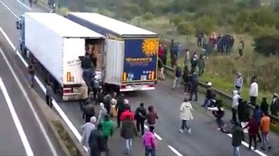 Migrants in Calais climbing into moving lorries thumbnail - DrivingOnly.com
