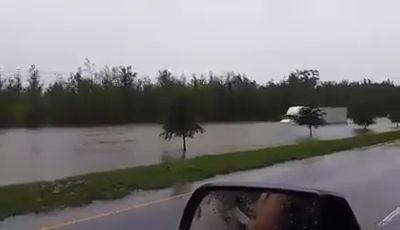 A truck driver driving through dangerously flooded road