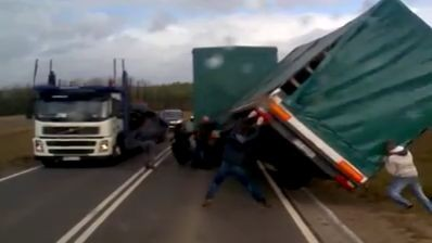 Fellow lorry drivers come to rescue a turned over trailer